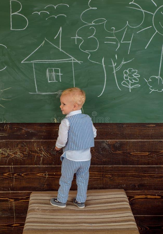 儿童在教室黑板的绘画图片 小男孩在小学学会图画图片 库存图片