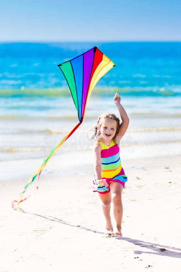 儿童在热带海滩的飞行风筝 免版税库存图片