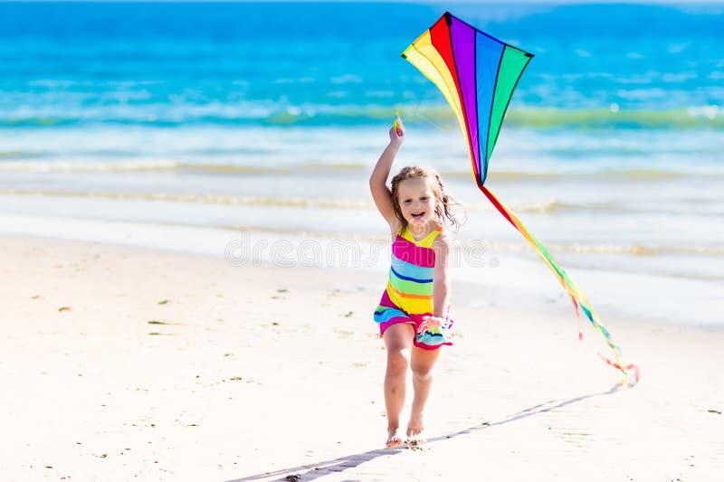 儿童在热带海滩的飞行风筝 图库摄影