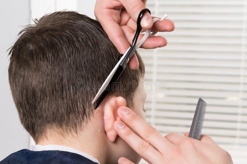 儿童在耳朵后的头发切口的过程有剪刀的,成水平长度 免版税图库摄影