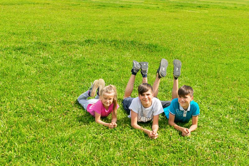 儿童在草的男孩和女孩谎言在绿色草甸在公园 夏天概念,在新鲜空气的儿童的比赛 免版税库存图片