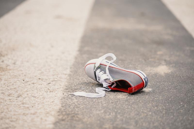儿童在街道上的` s鞋子在危险交通事件以后 免版税库存图片