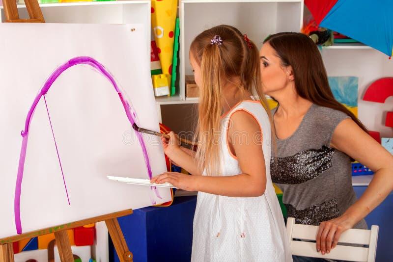 儿童在画架的画笔 小组与老师的孩子 免版税图库摄影