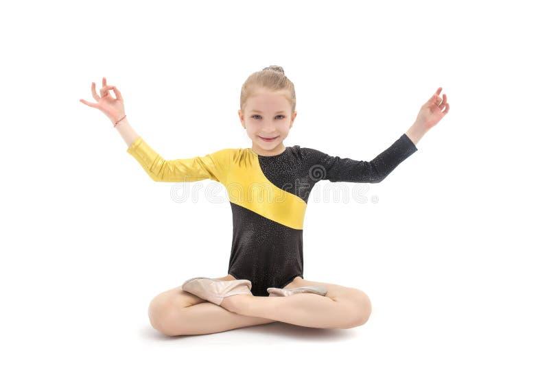 儿童坐在瑜伽位置的女孩体操运动员被隔绝在白色 免版税库存照片