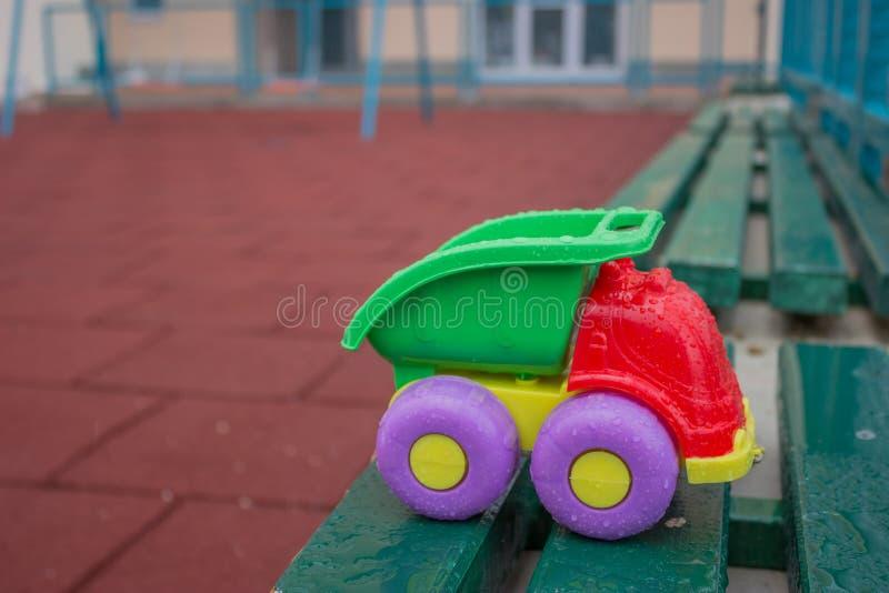儿童塑料玩具卡车在长凳的公园  库存图片