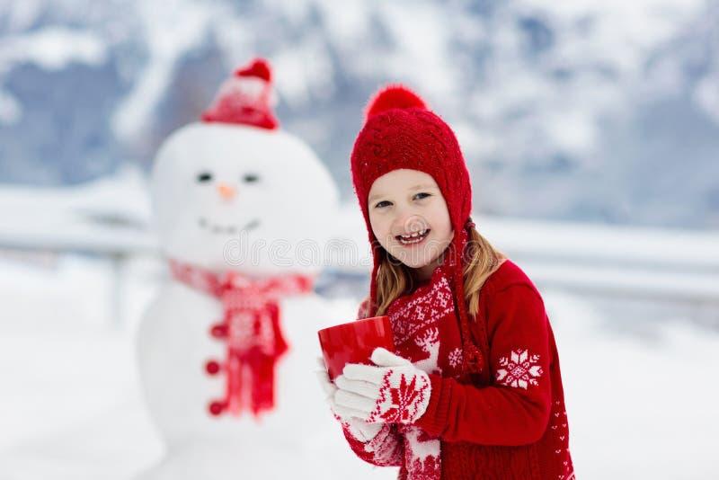 儿童大厦雪人 孩子修造雪人 使用户外在多雪的冬日的男孩和女孩 在圣诞节的室外家庭乐趣 图库摄影