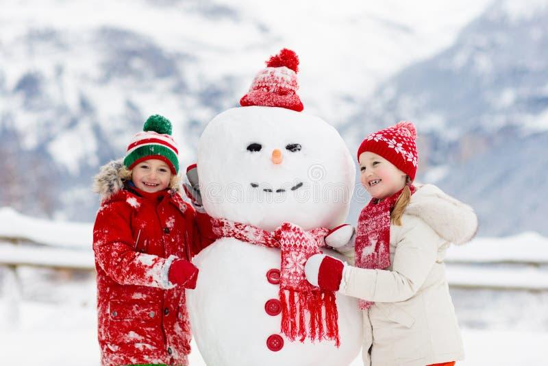 儿童大厦雪人 孩子修造雪人 使用户外在多雪的冬日的男孩和女孩 在圣诞节的室外家庭乐趣 免版税库存照片