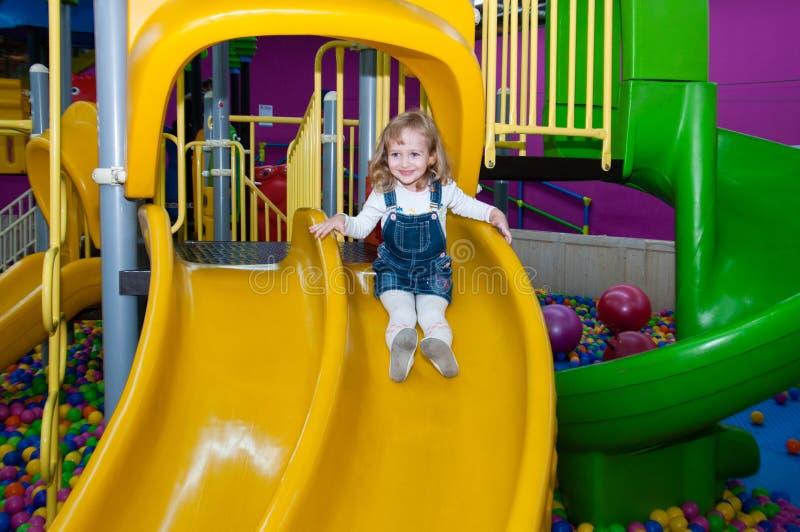 儿童女孩下降在操场的小山购物中心的 免版税库存照片