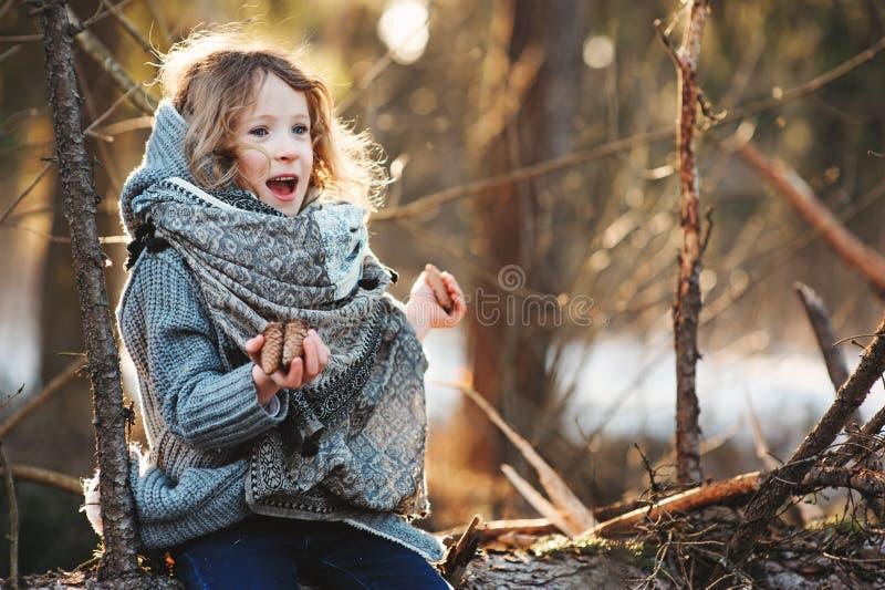 儿童女孩使用与在树注册冬天森林的杉木锥体 免版税库存照片