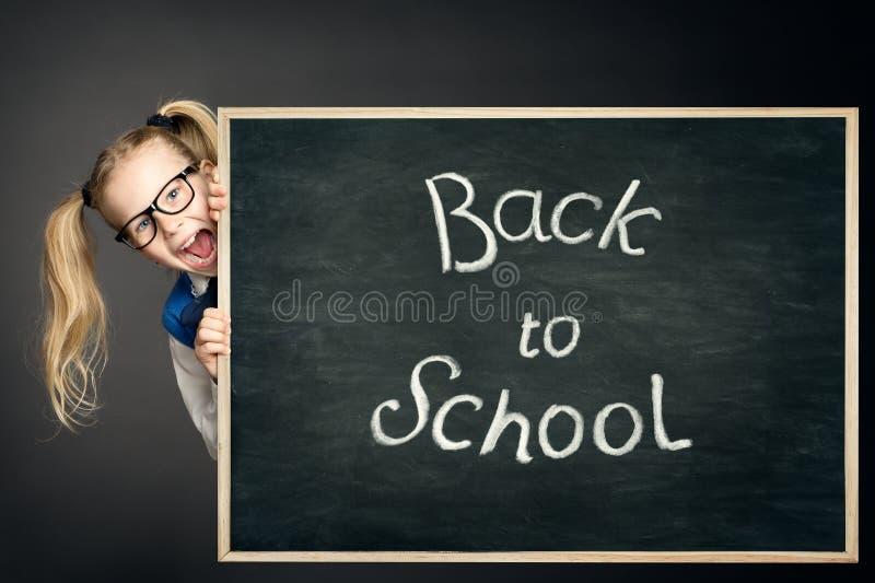 儿童女孩偷看在有粉笔画的学校黑板后,回到学校,愉快的孩子 免版税库存图片