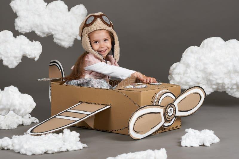 儿童女孩充当飞机由纸板箱和梦想成为做成飞行员,棉绒云彩在一灰色backgrou的 免版税库存图片
