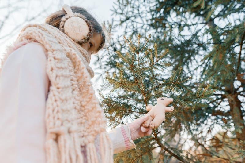 儿童女孩冬天室外画象在圣诞树附近的,微笑的女孩装饰与玩具,金黄小时的圣诞树 免版税库存图片