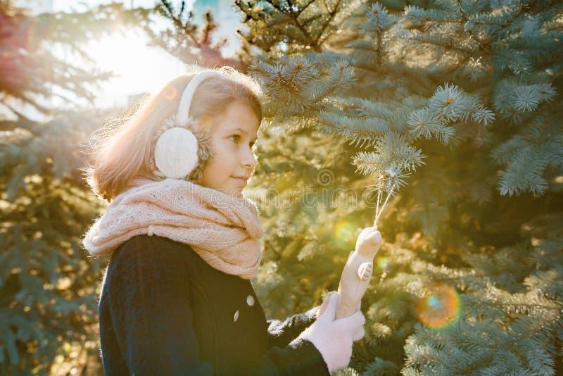 儿童女孩冬天室外画象在圣诞树附近的,微笑的女孩装饰与玩具,金黄小时的圣诞树 库存照片