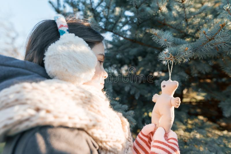 儿童女孩冬天室外画象在圣诞树附近的,微笑的女孩装饰与玩具,金黄小时的圣诞树 免版税库存照片