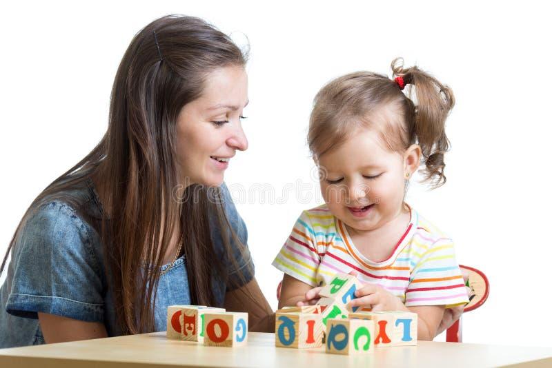 儿童女孩和妈妈获得演奏立方体玩具的乐趣 免版税库存照片