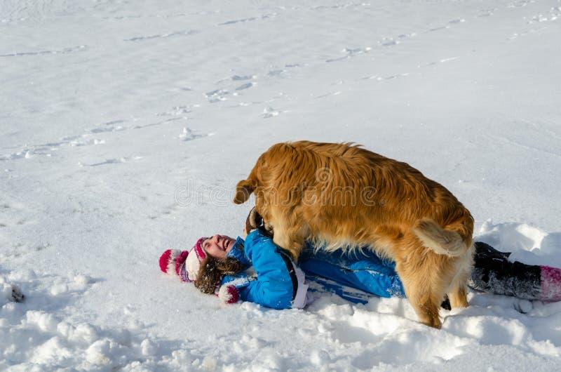 儿童女孩和狗在雪滚动 驱动乐趣爬犁冬天 图库摄影