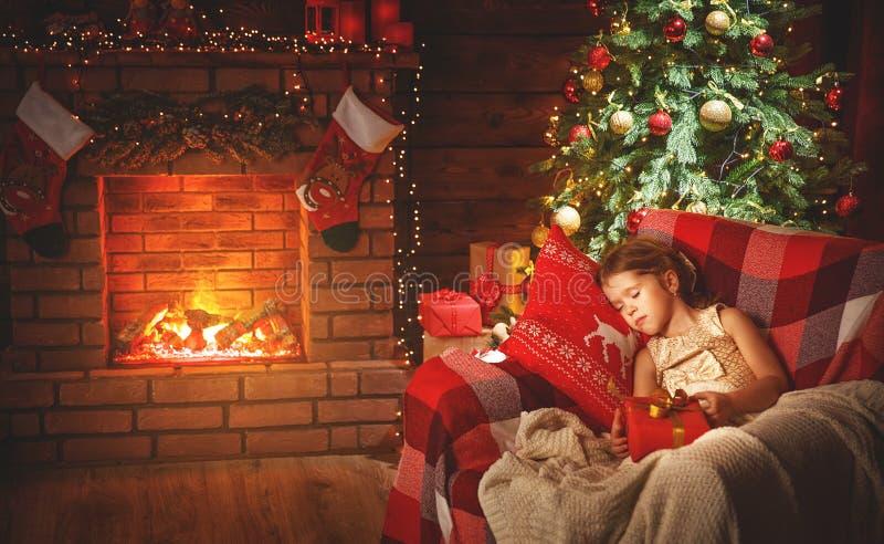 儿童女孩在圣诞树附近睡觉 库存照片