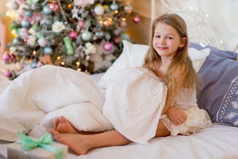 儿童女孩在她的床上醒在圣诞节早晨 图库摄影