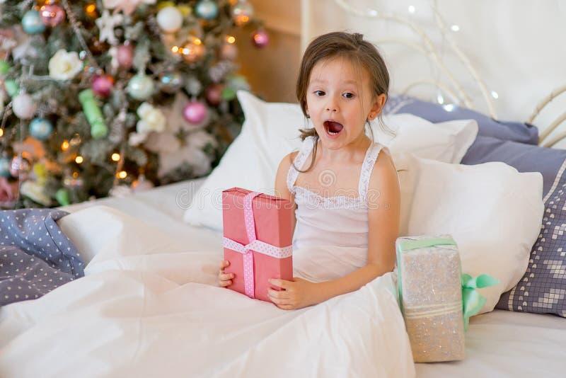 儿童女孩在她的床上醒在圣诞节早晨 免版税图库摄影