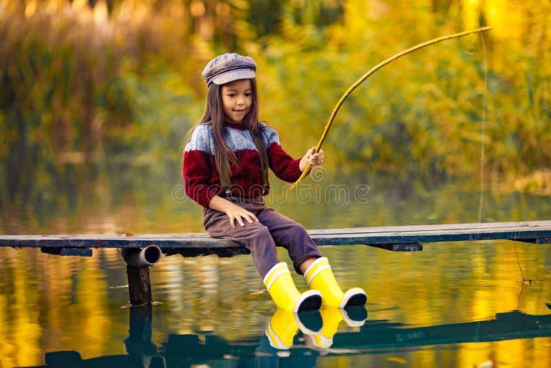 儿童女孩坐木钓鱼的桥梁并且抓在aut的鱼 免版税库存照片