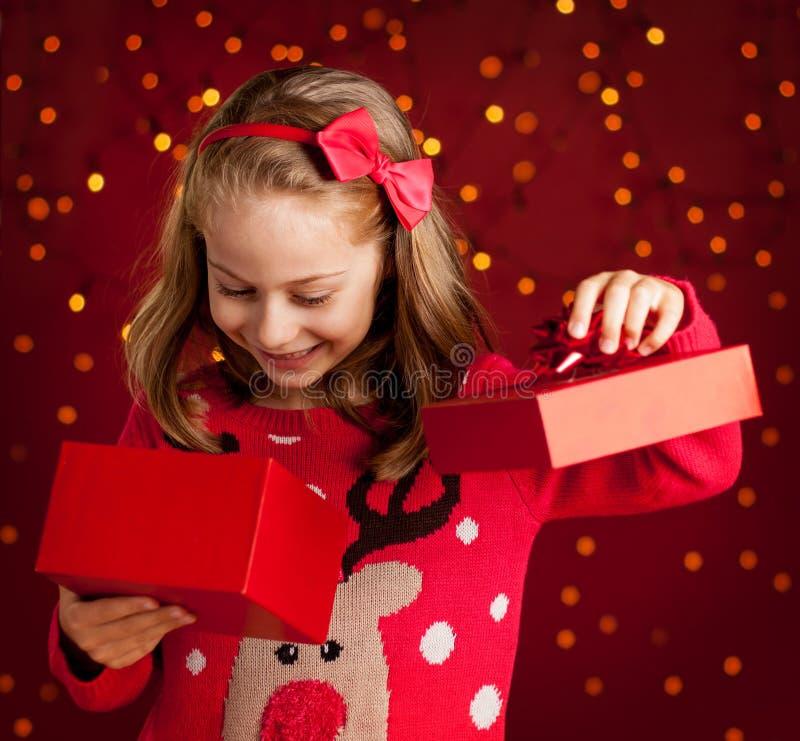 儿童女孩打开在深红的圣诞节礼物与光 免版税库存图片