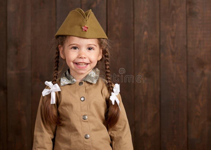 儿童女孩打扮作为减速火箭的军服的战士 库存照片