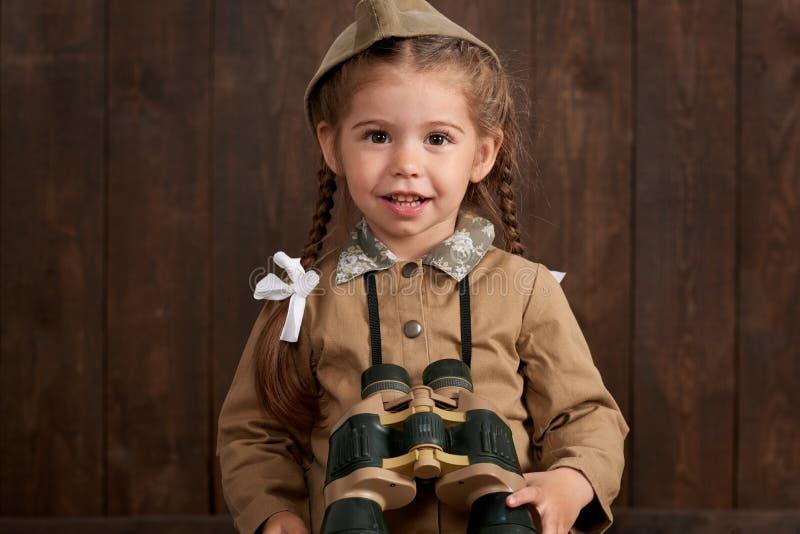 儿童女孩打扮作为减速火箭的军服的战士 库存图片