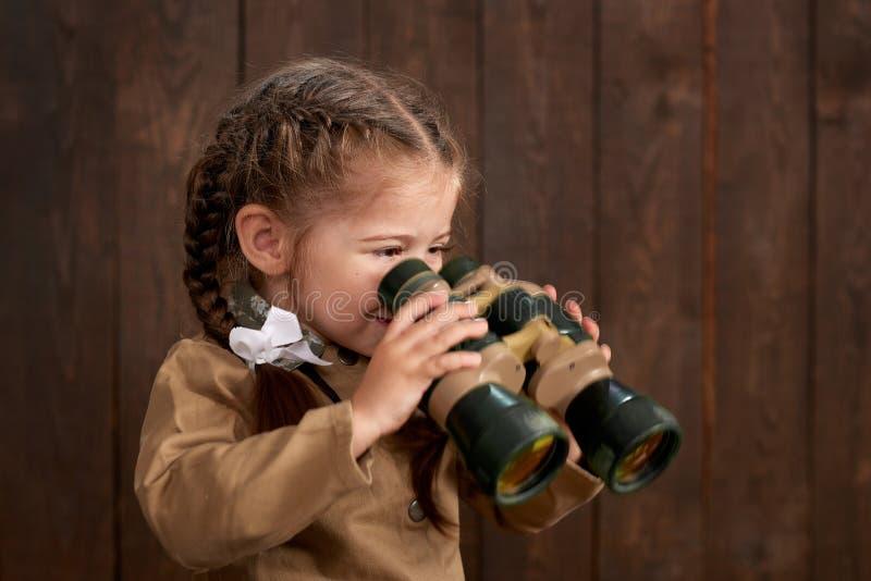 儿童女孩打扮作为减速火箭的军服的战士 免版税库存图片