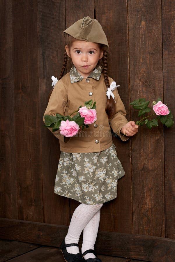 儿童女孩打扮作为减速火箭的军服的战士 图库摄影