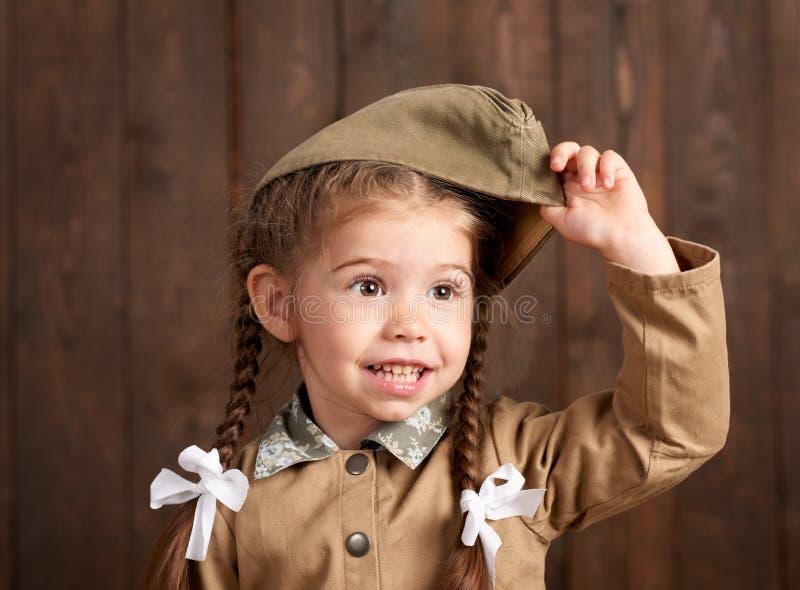 儿童女孩打扮作为减速火箭的军服的战士 免版税库存照片