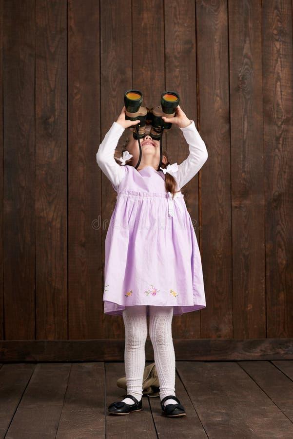 儿童女孩打扮作为减速火箭的军用哈里逊盖帽和桃红色礼服的战士 免版税库存照片