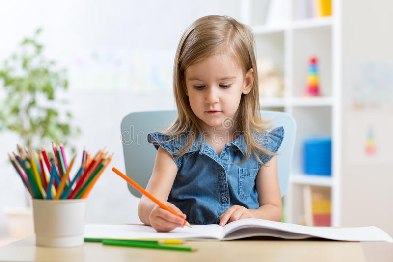 儿童女孩油漆在她的托儿所 免版税库存图片