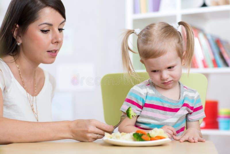 儿童女孩看充满憎恶健康菜 母亲说服她的女儿吃食物 免版税库存照片