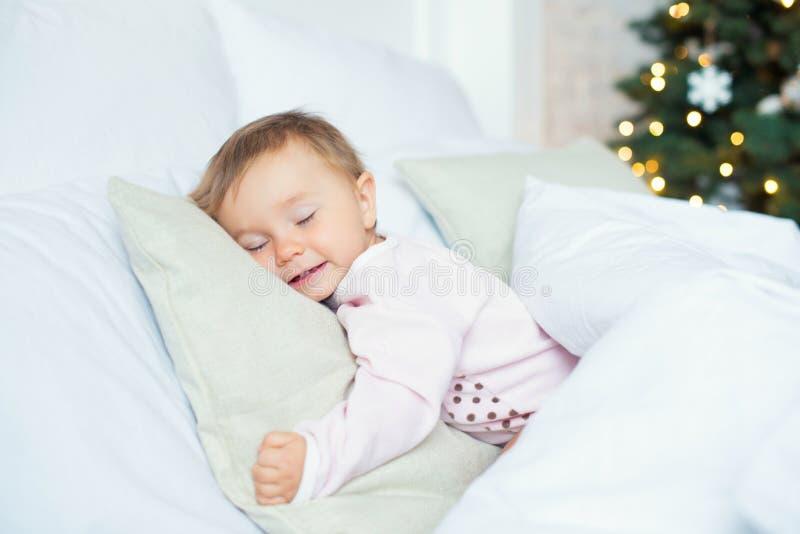 儿童女孩睡眠在她的床上在圣诞节早晨 免版税库存照片