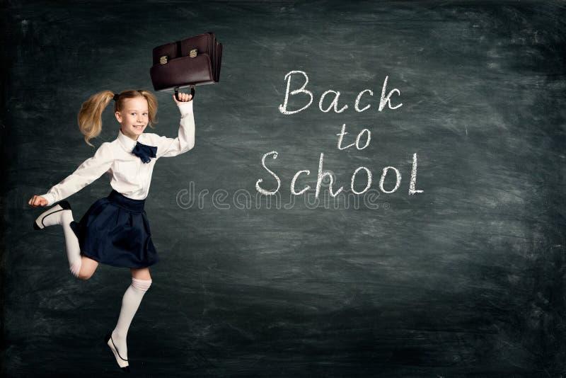 儿童女孩跑回到学校的,在减速火箭的礼服的学生孩子有跳跃在黑板的公文包的 库存图片