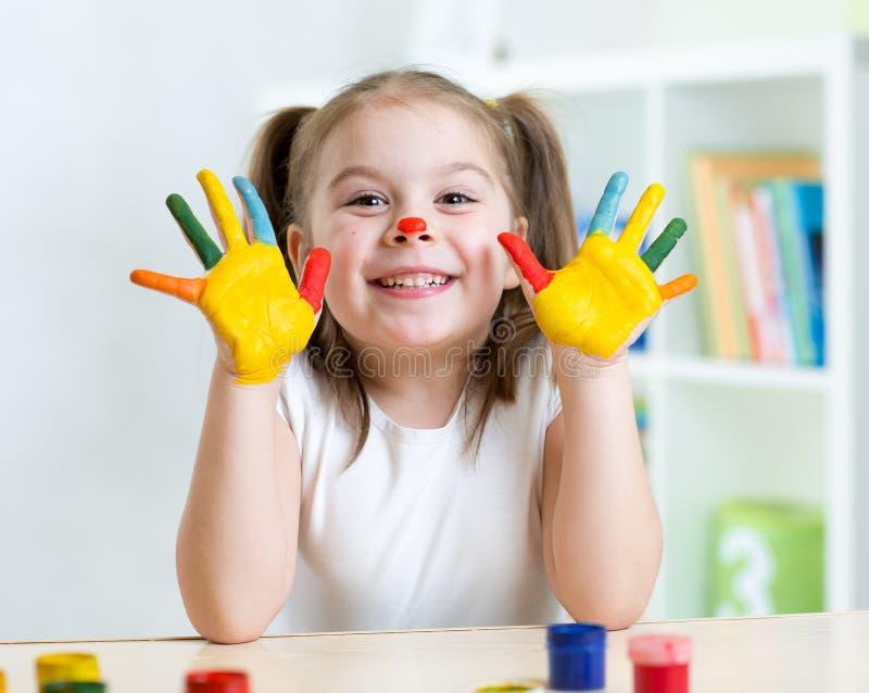 儿童女孩画象有被绘的面孔和手的 免版税库存图片
