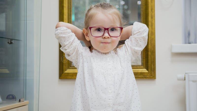 儿童女孩画象玻璃的-尝试时尚医疗玻璃购物在眼科学诊所的孩子 免版税库存照片
