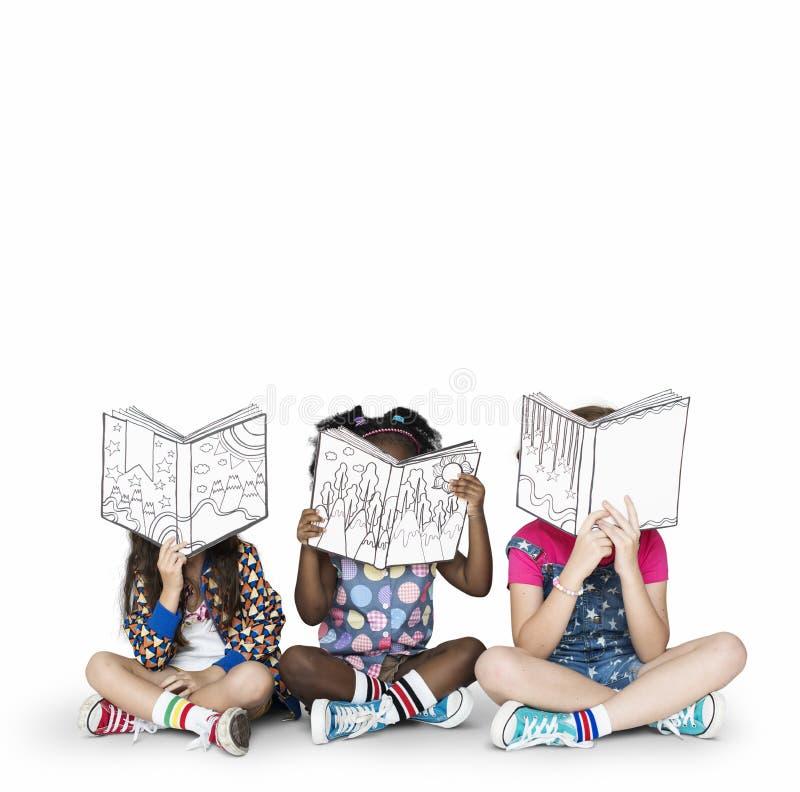 儿童女朋友阅读书教育统一性演播室概念 免版税库存照片