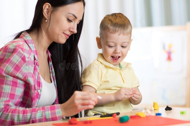 儿童孩子男孩和母亲在托儿所或幼儿园演奏五颜六色的黏土玩具 免版税图库摄影