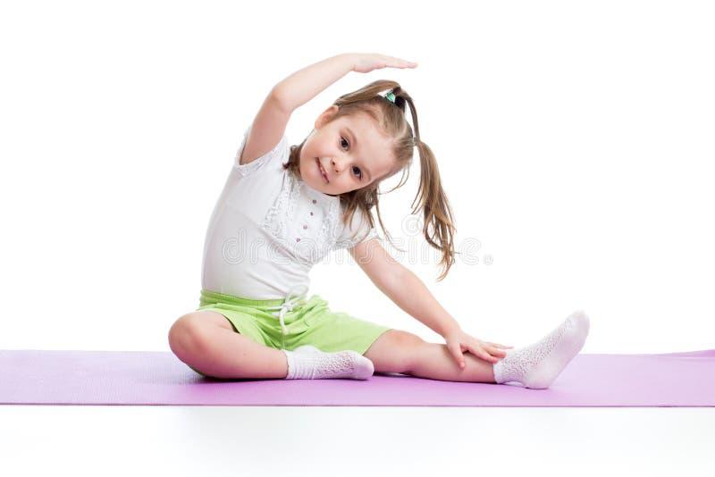 儿童实践的瑜伽,舒展在锻炼佩带的运动服 孩子被隔绝在白色背景 库存照片