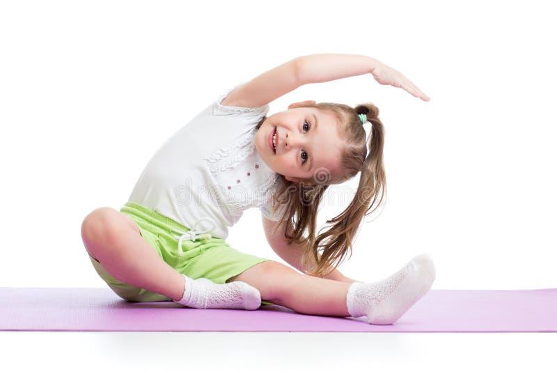 儿童实践的瑜伽,舒展在锻炼佩带的运动服 孩子被隔绝在白色背景 免版税图库摄影