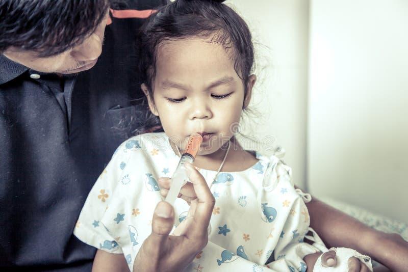 儿童小女孩得到与一个注射器的医学在她的嘴 免版税图库摄影