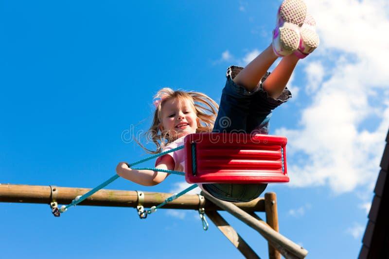 儿童庭院女孩摇摆 免版税库存图片