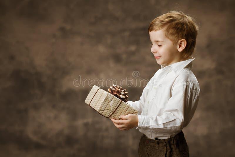 儿童当前礼物盒 拿着giftbox的愉快的孩子 图库摄影