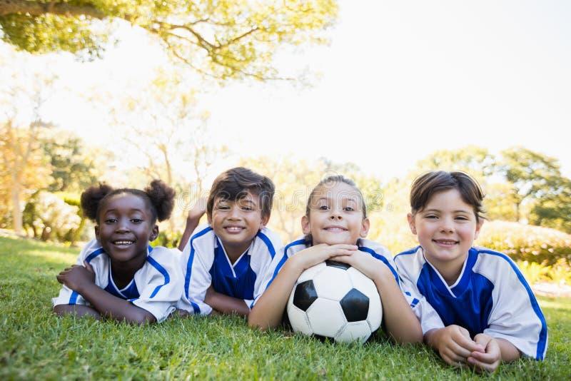 儿童微笑对照相机的足球队员,当说谎在地板上时 库存图片