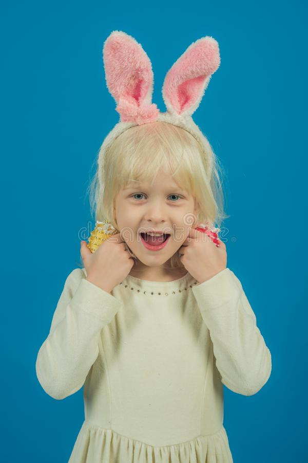 儿童微笑用手工制造鸡蛋 兔宝宝耳朵的女孩,复活节 有魄力的淡色趋向 孩子秀丽和时尚神色 库存图片