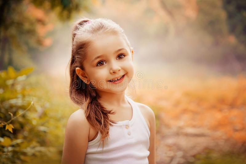 儿童微笑的幸福概念 一个逗人喜爱的微笑的小女孩的室外画象 免版税库存照片