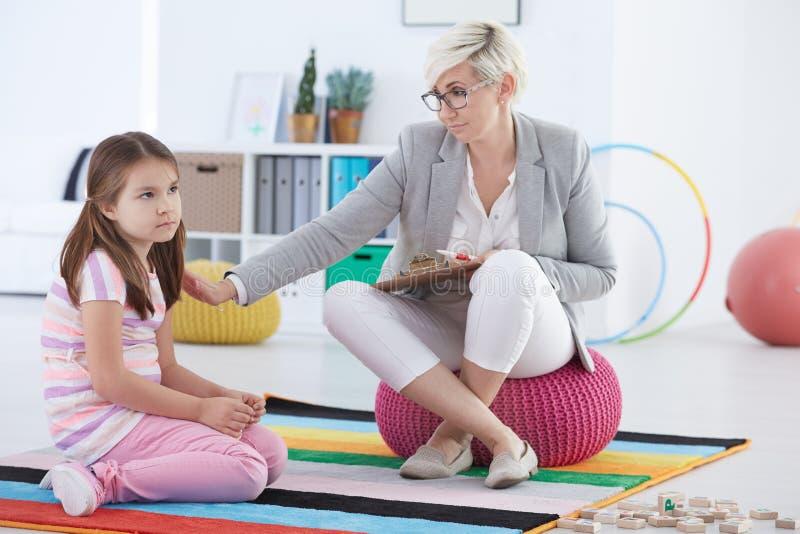 儿童心理学家和哀伤的女孩 免版税库存图片
