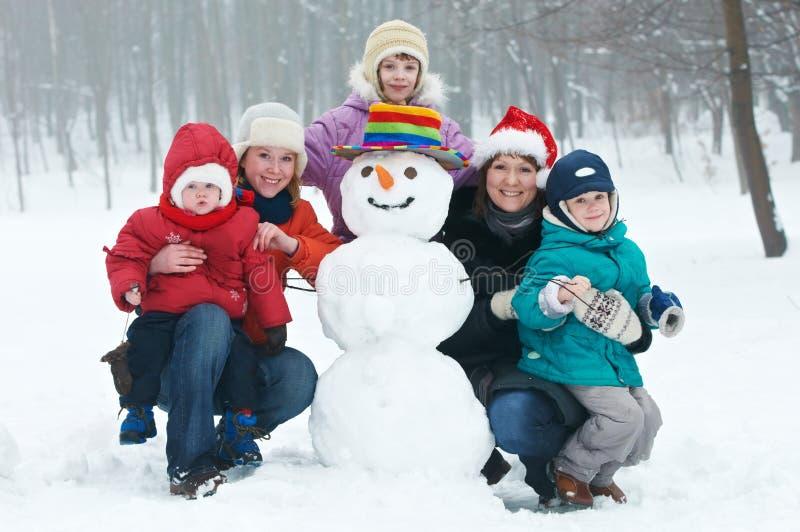 儿童愉快的雪人冬天妇女 免版税库存图片
