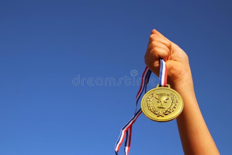 儿童手上升了,拿着金牌反对天空 教育、成功、成就、奖和胜利概念 图库摄影
